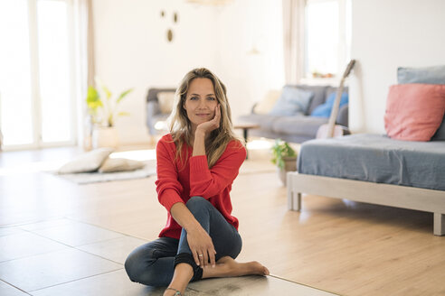 Portrait of smiling woman sitting on the floor at home - SBOF01924