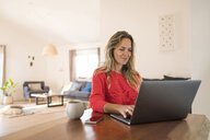 Woman using laptop on dining table at home - SBOF01933