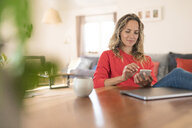 Woman using cell phone on dining table at home - SBOF01936