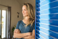 Woman leaning at open window at home looking sideways - SBOF01951