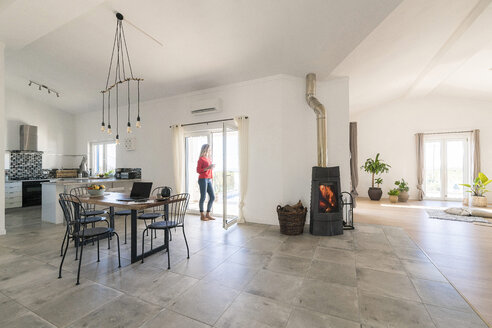 Woman standing in door frame of modern living room with fireplace - SBOF01954