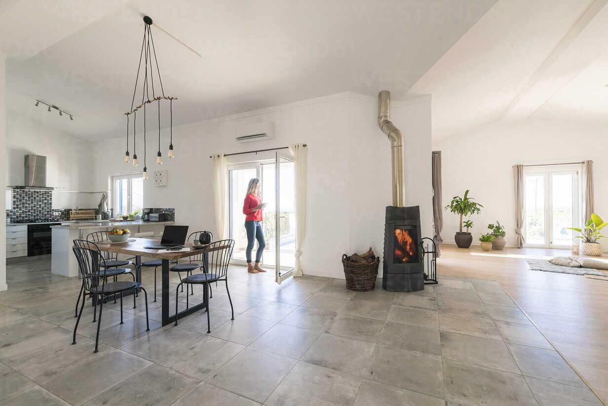 Woman standing in door frame of modern living room with fireplace - SBOF01954 - Steve Brookland/Westend61