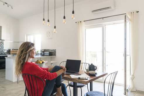Woman using laptop on dining table in modern home - SBOF01957