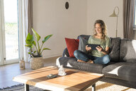 Happy woman realxing on couch at home using tablet - SBOF01966