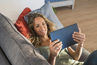 Happy woman realxing on couch at home using tablet - SBOF01969