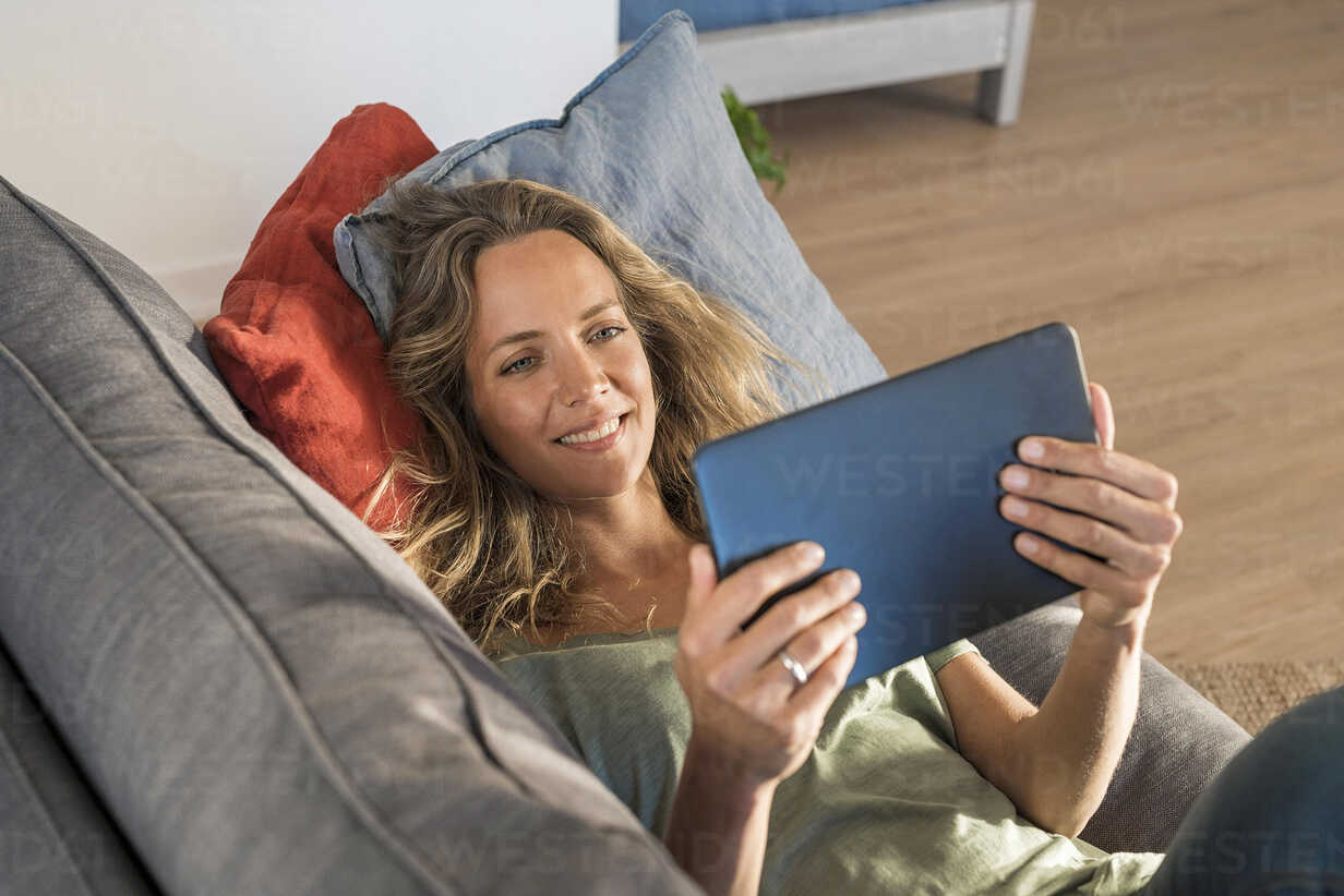 Happy woman realxing on couch at home using tablet - SBOF01969 - Steve Brookland/Westend61