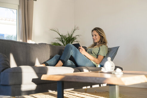 Smiling woman realxing on couch at home using tablet - SBOF01972