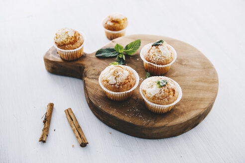 Home-baked muffins with cinnamon and mint on wooden board - ERRF00809