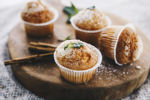 Home-baked muffins with cinnamon and mint on wooden board - ERRF00815