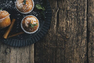 Home-baked muffins with cinnamon and mint on plate - ERRF00818