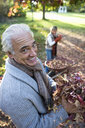 Senior couple collecting autumn leaves in wheelbarrow in garden, focus on man, smiling, portrait - JUIF00065