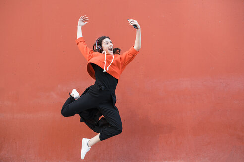 Young contemporary dancer jumping and using smartphone in front of a red wall - JRFF02887