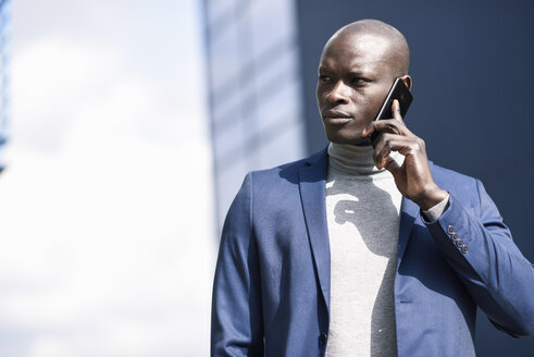 Spain, Andalusia, Malaga. Black businessman wearing a blue suit in an office building environment talking on a smart phone. Business concept. - JSMF00875