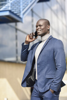 Portrait of content businessman on the phone wearing blue suit - JSMF00881