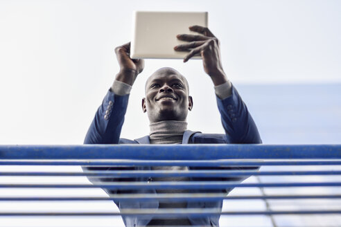 Portrait of smiling businessman leaning on railing using digital tablet - JSMF00884
