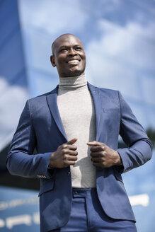 Portrait of content businessman wearing blue suit and grey turtleneck pullover - JSMF00893