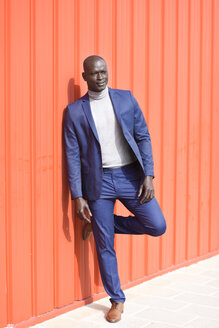 Spain, Andalusia, Malaga. Self-confident black businessman wearing a blue suit on urban orange wall. Business concept. - JSMF00896