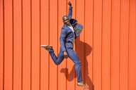 Smiling businessman jumping in the air in front of orange wall - JSMF00899