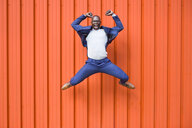 Successfull businessman jumping in the air in front of orange wall screaming - JSMF00902