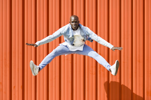 Man wearing casual denim clothes jumping in the air in front of orange wall - JSMF00929