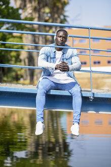 Portrait of man wearing casual denim clothes sitting on footbridge listening music with wireless headphones - JSMF00935
