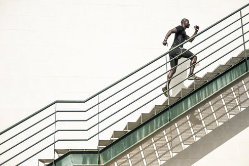 Spain, Andalusia, Malaga. Black man with athletic body running up the stairs in sportswear. Fitness concept. - JSMF00938