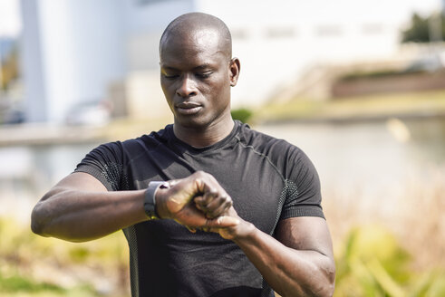 Spain, Andalusia, Malaga. Black man using smartwatch device before doing exercise. Fitness concept. - JSMF00944