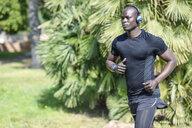 Spain, man in black sportswear running in a park listening music with wireless headphones - JSMF00950