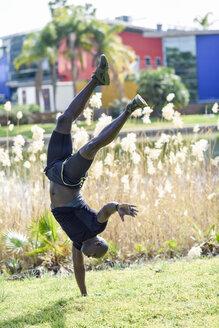 Man in black sportswear doing one-handed handstand on a meadow - JSMF00956