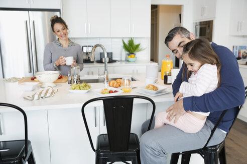 Father hugging daughter enjoying breakfast in morning kitchen - HEROF30613