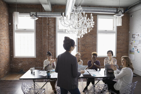 Female designers meeting and clapping in conference room - HEROF30700