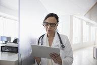 Female doctor using digital tablet in clinic corridor - HEROF30715