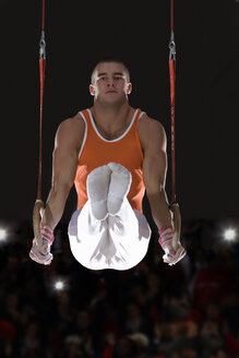 Male gymnast performing on gymnastic rings, portrait, low angle view - JUIF00218