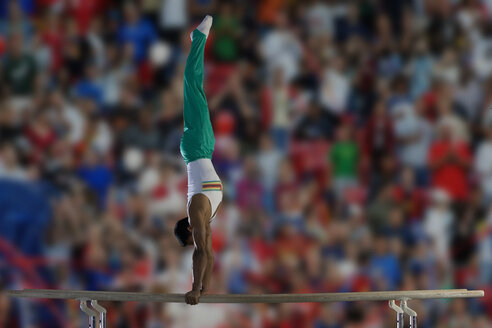 Male gymnast performing handstand on parallel bars, side view - JUIF00239