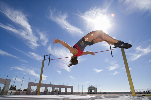 Female athlete jumping over bar, low angle view (lens flare) - JUIF00248