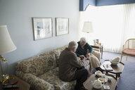Senior couple knitting in living room - HEROF30844