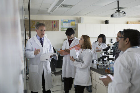 Science professor leading college students at whiteboard in laboratory - HEROF30991