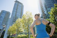 Runner with hands on hips below city highrise buildings - HEROF31000