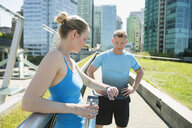 Runners resting checking smart watch on city boardwalk - HEROF31006