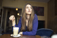 Young woman sitting at table in a cafe looking sideways - PNEF01315