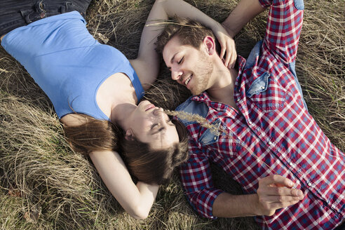 Happy young couple lying in meadow - PNEF01318