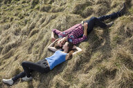 Happy young couple lying in meadow - PNEF01321