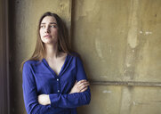 Young woman standing at a wall looking sideways - PNEF01324