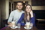 Portrait of young couple in a cafe with milk froth on lips - PNEF01327