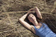 Portrait of relaxed young woman lying in meadow - PNEF01330