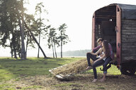Happy young couple sitting on trailer in the countryside - PNEF01333