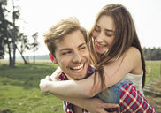 Happy young man carrying girlfriend piggyback on meadow - PNEF01336