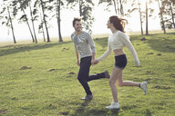Happy young couple running hand in hand on meadow - PNEF01339