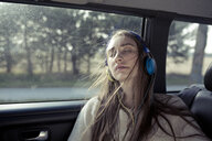 Young woman with windswept hair in a car wearing headphones - PNEF01342