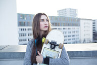 Serious young woman with skateboard and headphones in the city looking sideways - PNEF01354